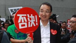 """王征手持""""否决""""标语,在政府总部集会力阻增发免费电视牌照。图片来源:香港网路大典"""